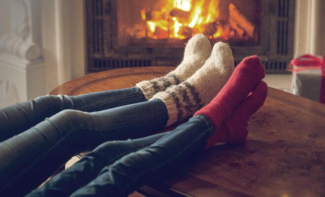 Kalte Füße: Ein Paar vor dem Kamin im Winter