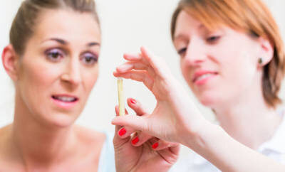 HCG-Diät: Zwei Frauen betrachten ein Fläschchen mit hCG-Globuli.