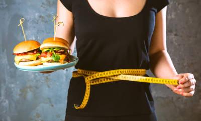 Eine Frau mit zwei großen Burgern in der Hand. Sie ist von Binge Eating betroffen, einer Esstörung, bei der es zu unkontrollierten Essattacken kommt.