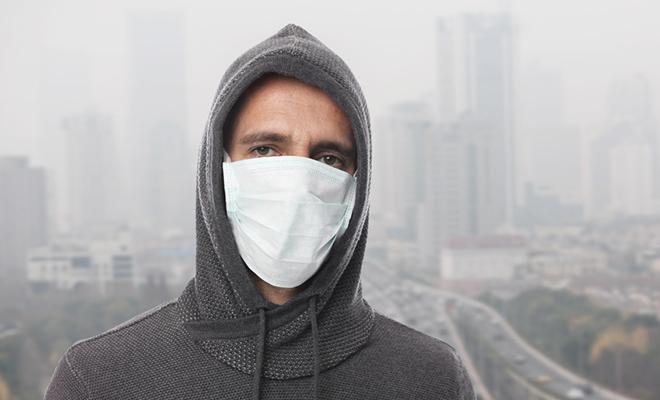 Mann mit Schutzmaske gegen Feinstaub.