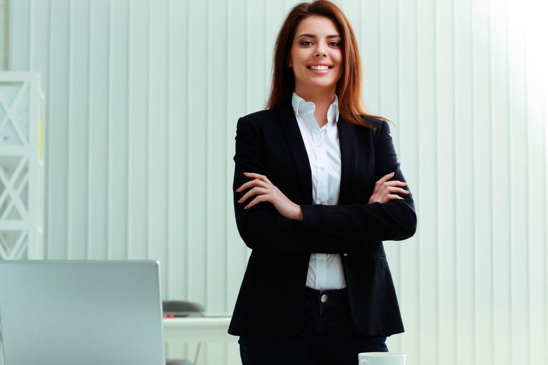 Selbstbewusste Frau an Ihrem Arbeitsplatz mit verschrenkten Armen
