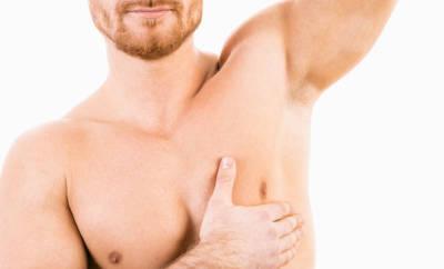 Gynäkomastie: Ein Mann fasst sich an die Brust