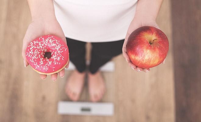 Frau auf der Waage: Donut oder Apfel?