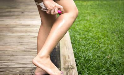 Frau verwendet Insektenspray am Bein