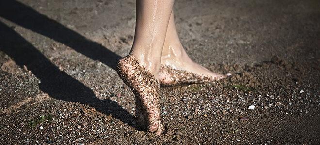 Füße gehen durch Sand
