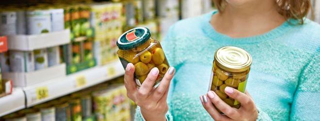 Frau kauft Oliven ein.