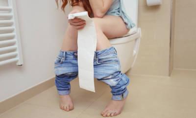 frau sitzt auf der toilette
