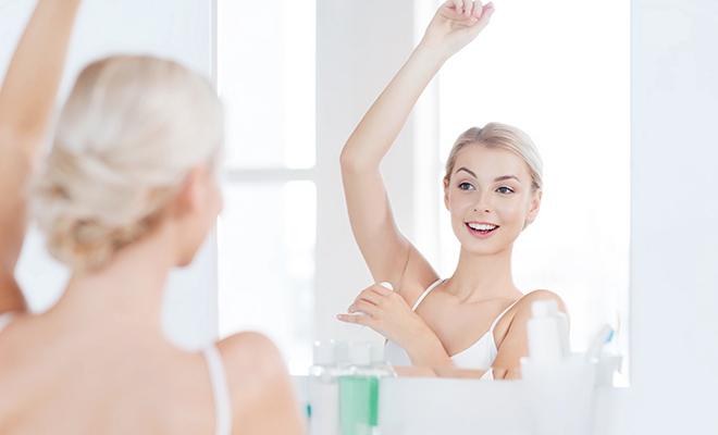 Frau steht vor dem Spiegel und benutzt Deodorant
