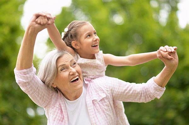 Großmutter trägt ihre Enkeltochter Huckepack und hat Spaß.