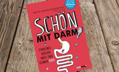 """Buch """"Schön mit Darm"""" vor Holzhintergrund."""