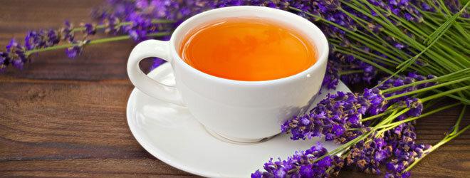 Eine Tasse Tee mit Lavendel daneben.
