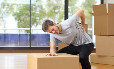 Mann der Paket hebt und offenbar starke Rückenschmerzen hat