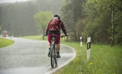 Mann fährt auf dem Fahrrad im strömenden Regen