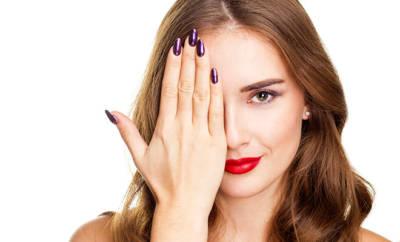 Frau mit lila künstlichen Fingernägeln hebt sich die Hand vors Auge.