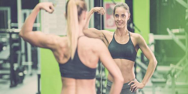 Muskulöse Frau posiert vor Spiegel im Fitnessstudio.