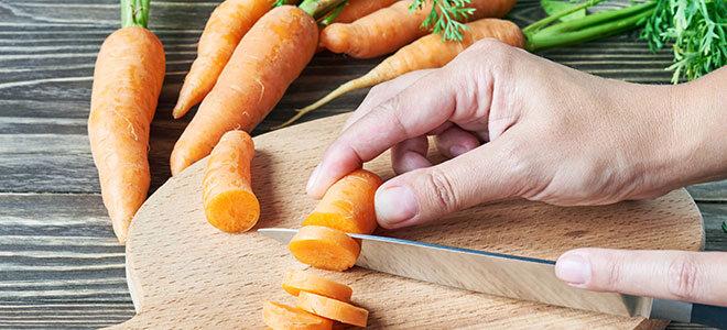 Karotenn werden auf Schneidebrett geschnitten.