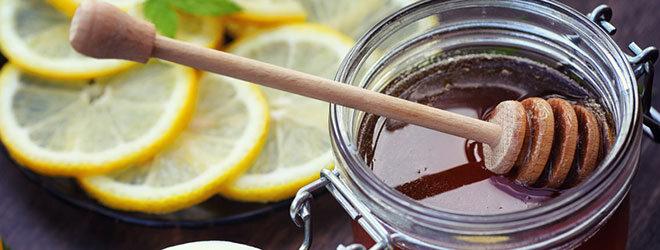Glas Honig mit Zitronenscheiben daneben.