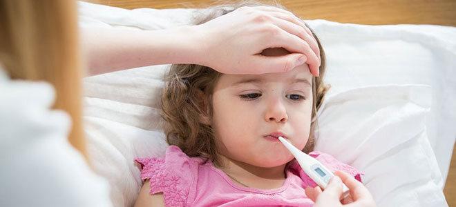 Keines Mädchen liegt im Bett mit Thermometer im Mund und Hand auf der Stirn.