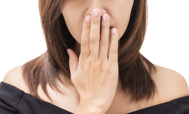 Frau hält sich Hand vor den Mund