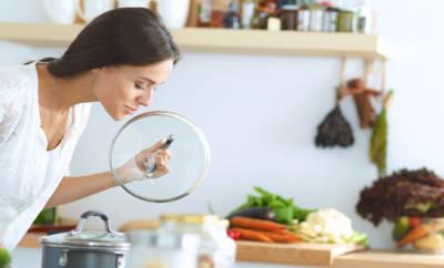 Frau, die kocht, beugt sich über Kochtopf und riecht.