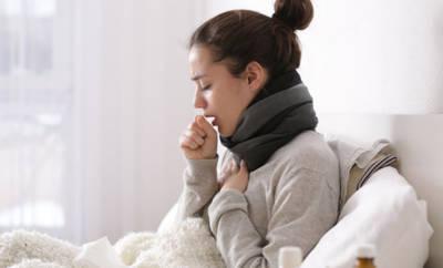 Frau, die krank im Bett sitzt und hustet.