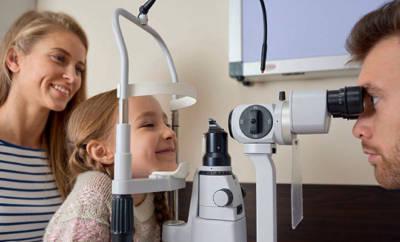 Kleines Mädchen mit Mutter bei augenärztlicher Untersuchung.