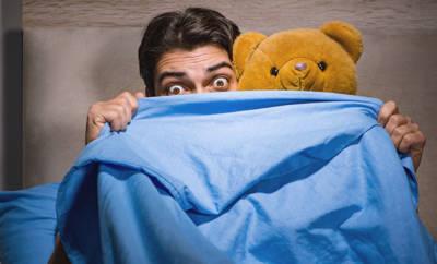 Mann versteckt sich hinter einer Decke