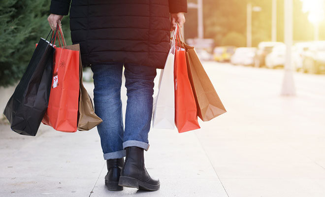 Frau läuft mit mehreren Einkaufstüten in der Hand.