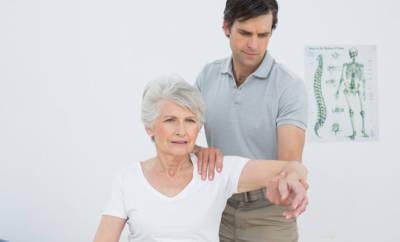 Ein Arzt untersucht eine Seniorin auf das Impingement-Syndrom an ihrer Schulter.