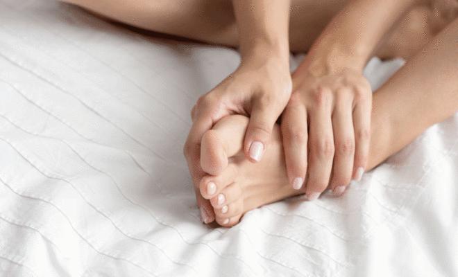 Frau massiert sich die Beine