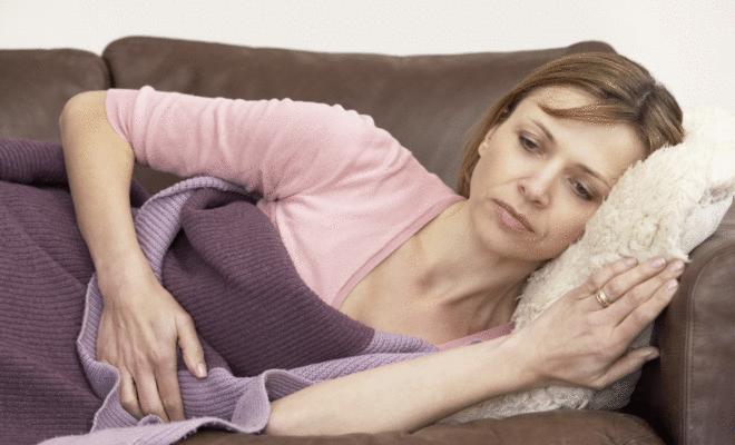 Frau liegt mit Übelkeit auf dem Sofa