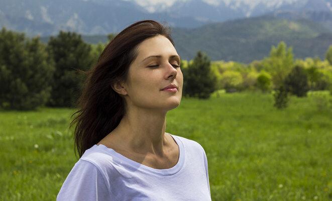 Frau vor einer Bergkulisse, die tief durchatmet.