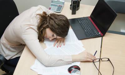 Eine junge Frau hat ihren Kopf erschöpft auf den Bürotisch gelegt. Nach dem Mittagessen ist sie in ein Leistungstief gerutscht.