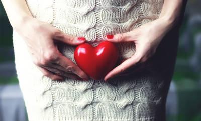 Frau hält ein rotes Herz vor Ihren Bauch auf höhe der Gebärmutter