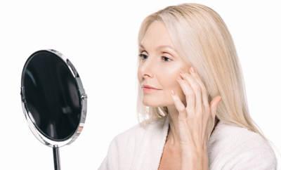 Frau mittleren Alters betrachtet sich im Spiegel.