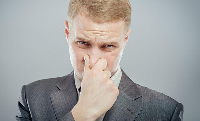 blonder Mann im Anzug hält sich die Nase zu.