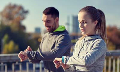 Junges Paar, das beim Joggen auf den Fitnesstracker schaut.