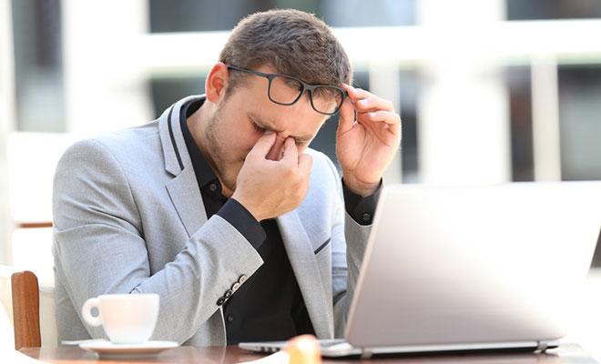 Übermüdeter Geschäftsmann sitzt vor Laptop und reibt sich die Augen.