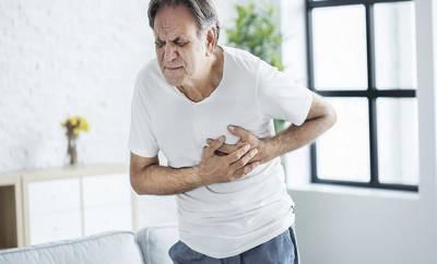Älterer Mann lang sich mit schmerzverzerrten Gesicht an die Brust.