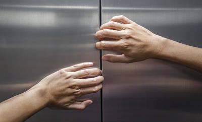 Hände die versuchen geschlossene Aufzugtür zu öffnen.