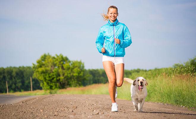 Frau joggt mit Hund.