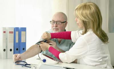Ärztin misst Blutdruck von Mann.
