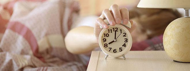 Müde Frau stellt den Wecker ab