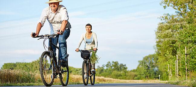 Älteres Pärchen das Fahrrad fährt und sichtlich Spaß dabei hat.