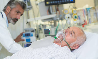 Älterer Mann der mit Sauerstoffmaske im Krankenhaus liegt.