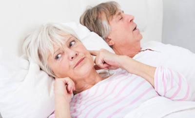Älteres Pärchen liegt im Bett, Frau hält sich die Ohren zu, da Mann schnarcht.