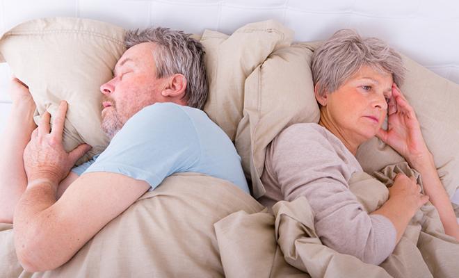 Älteres Paar, das von einander abgedreht im Bett liegt.