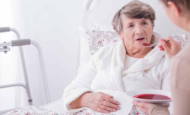 Ältere Frau, die im Bett liegt und gefüttert wird.
