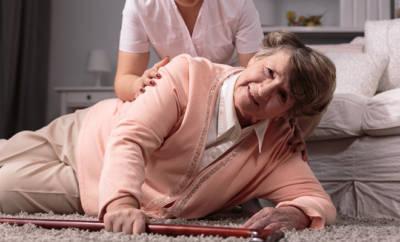 Ältere Frau, die zu Boden gestürzt ist.
