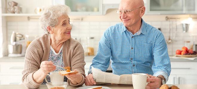 Älteres Ehepaar, das gemeinsam frühstückt.